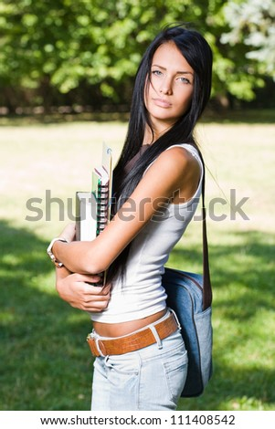 Outdoors portrait of a gorgeous young brunette student.