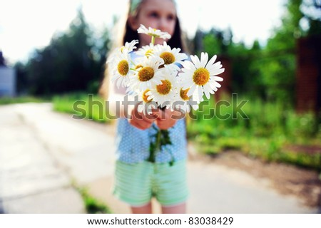 Outdoors portrait of adorable child girl showing daisies, focus on flowers - stock photo
