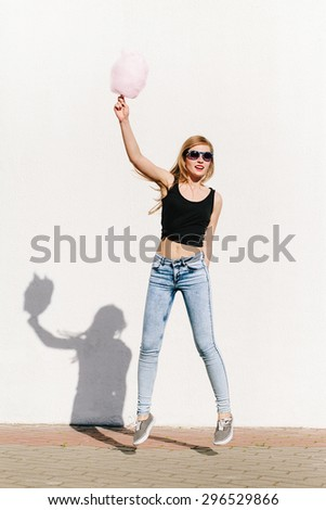 Outdoors portrait of beautiful blonde girl having fun and jumping with cotton candy on the street. Casual style, wearing sunglasses, red lips - stock photo