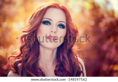 Outdoors portrait of beautiful woman with red hair and smoky eyes makeup - stock photo
