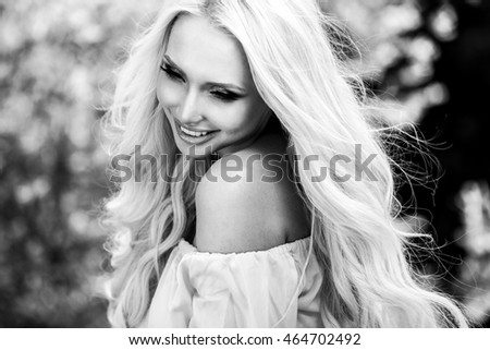 Outdoors portrait of beautiful young blond woman. Black-white photo.