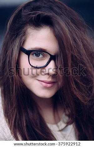 Outdoors portrait of beautiful young brunette girl. Selective focus. - stock photo