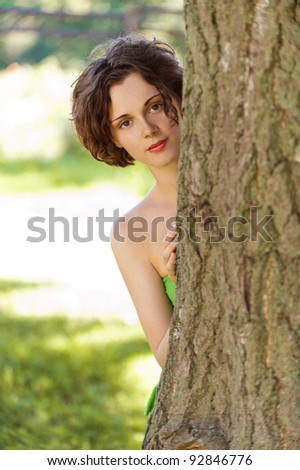 outdoors portrait of beautiful young curly woman looking from behind the tree trunk - stock photo