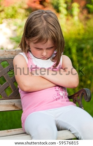 Outdoors portrait of small cute girl with offended look - stock photo