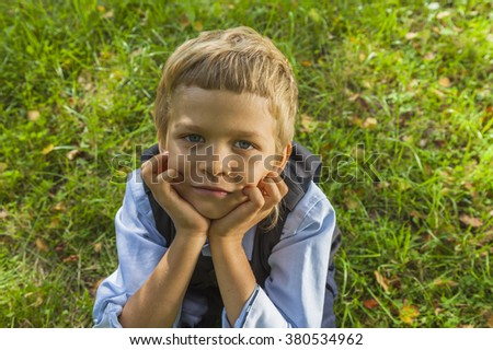 Outdoors portrait of smart child boy on natural green background. - stock photo