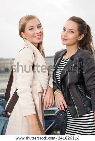 Outdoors portrait of two fashionable attractive student girls.