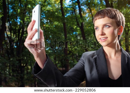 Outdoors portrait of Young and pretty caucasian woman in formalwear taking photo smiling with her smart phone.  - stock photo