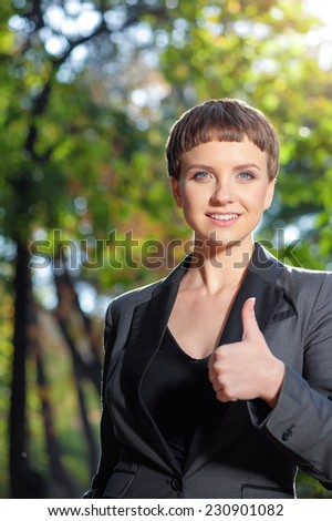 Outdoors portrait of young beautiful confident woman in formalwear happily raises her thumb up and smiling, on green background summer nature. - stock photo