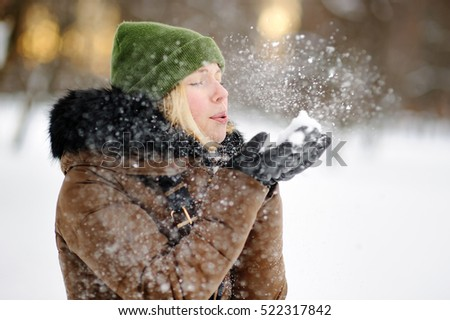 Outdoors portrait of young beautiful woman playing with snow. Winter mystery