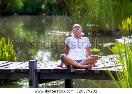 outdoors relaxation - beautiful young yoga woman enjoying to relax on a wooden bridge with green foreground and water background, summer exotic daylight - stock photo