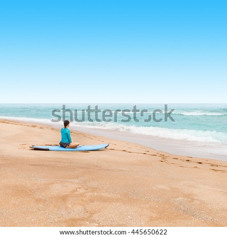 Outdoors shot of a lady surfer waiting at a seashore for a big waves to come - stock photo