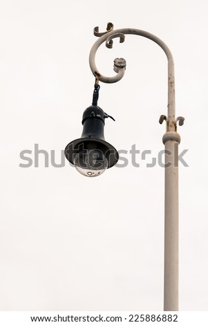 Outdoors shot of a streetlight over a grey cloudy sky.