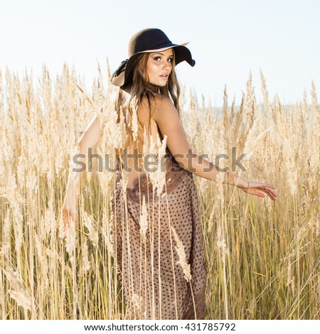 Outdoors sunrise shot of a beautiful model making her way through tallgrass - stock photo
