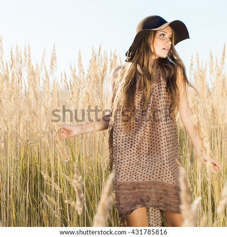 Outdoors sunrise shot of a beautiful young model walking through tallgrass meadow - stock photo
