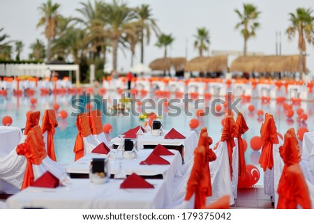 Outdoors under palm trees by the pool decorated with orange bows banquet tables