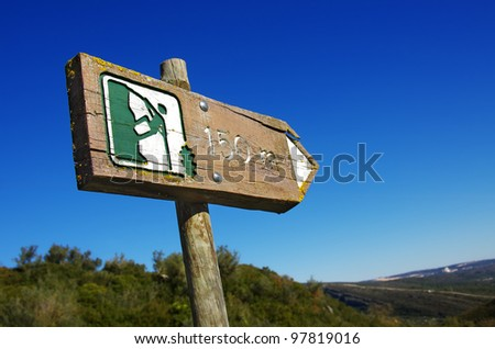 Outdoors with old wooden sign indicating directions to a mountaineering site - stock photo