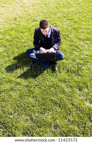 Outdoors working businessman on green grass - stock photo