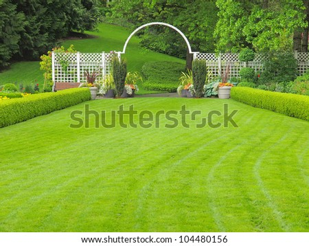 Outdor wedding place in the garden, with grass lawn and white arc