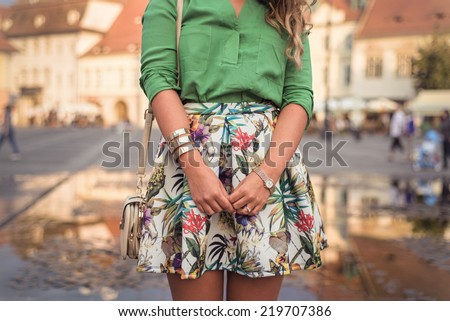 Outfit details of fashion elegant stylish woman posing on city streets in summer evening weather. Sensual blonde vogue girl street style shooting - stock photo