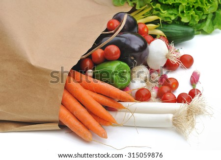 Outgoing fresh vegetables of a paper bag of groceries on white background