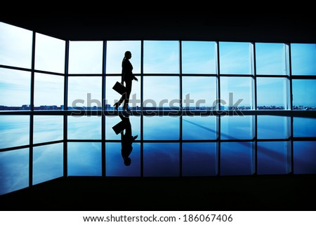 Outline of office worker with briefcase walking along window - stock photo