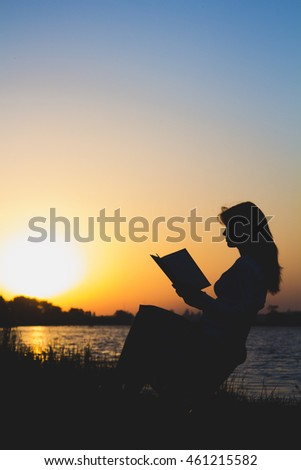 outlines of a beautiful young woman with a book by the river at dawn of the day