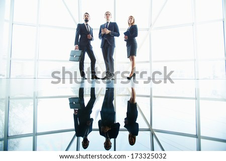 Outlines of successful business partners standing against window in office building - stock photo