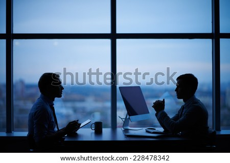 Outlines of two businessmen working late in office