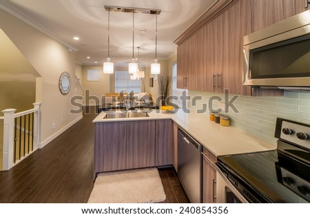 Outlook at the luxury and nicely decorated modern living set: kitchen, decorated dining table and the living room at the back. Interior design.