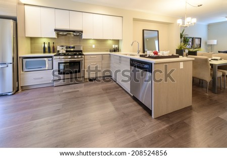Outlook at the luxury modern kitchen with the dining table at the back in a brand new house. Interior design. - stock photo