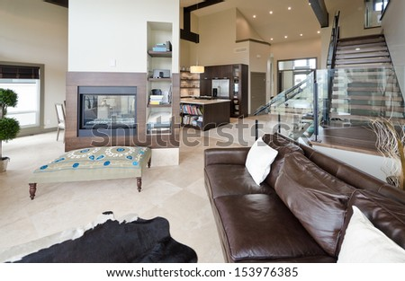 Outlook at the luxury spacious modern living room with the fireplace and stairs to the upper