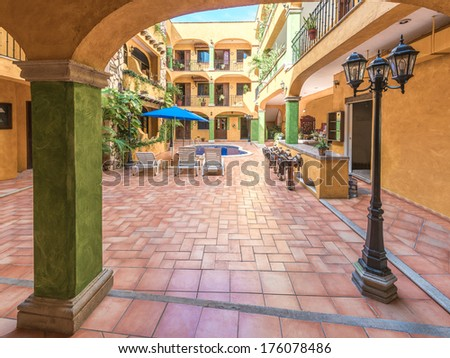 Outlook through the arch at the hotel in traditional colonial style. Inner court, plaza, yard of luxury caribbean, mexican hotel with swimming pool, lounges, bar counter. Interior, exterior design.
