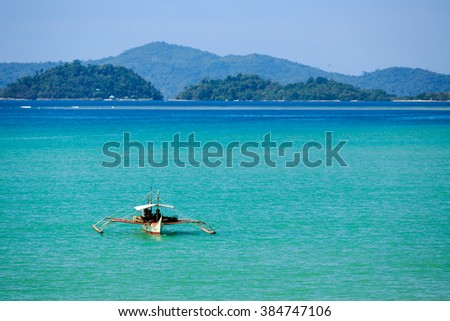 Outrigger canoe approaching land in beautiful Bay in Philippines - stock photo