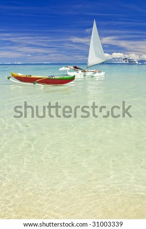 Outrigger canoes on white sand beach in the south pacific. Huahine, French Polynesia - stock photo