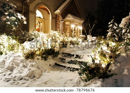 Outside Christmas lights line path to a front door on a snowy evening - stock photo