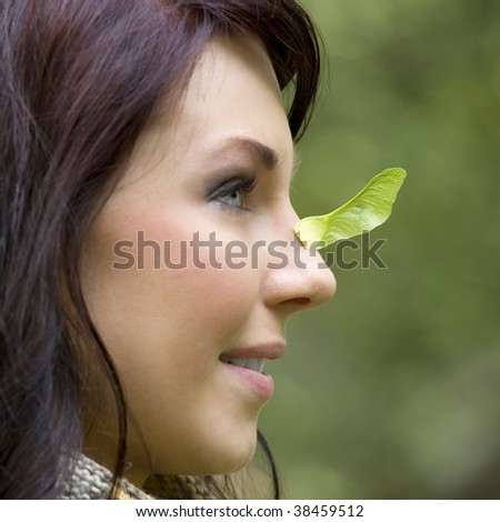 outside close up portrait of a pretty girl playing with a leaf on her nose - stock photo