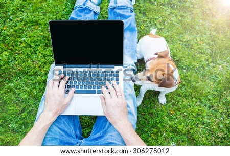 Outside laptop typing chatting with dog. Summer work. - stock photo
