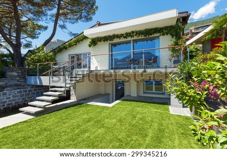 Outside of villa with garden on the lake - stock photo