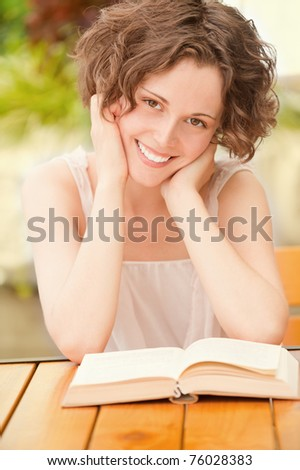 outside portrait of beautiful curly young woman sitting at the park cafe table and reading book - stock photo