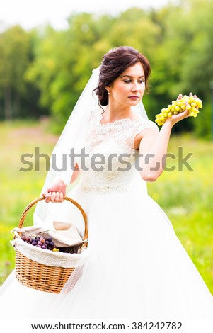 Outside portrait of beautiful young bride with grapes in a park - stock photo