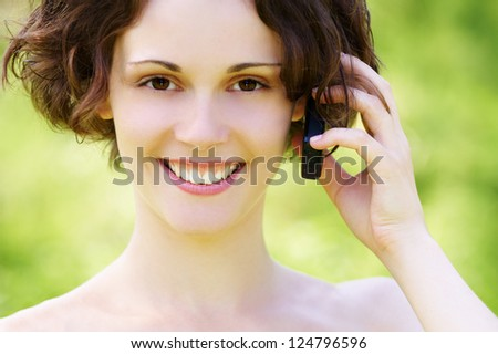 outside portrait of beautiful young curly woman talking over mobile phone in park - stock photo