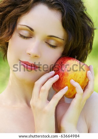 outside portrait of beautiful young curly woman with eyes shut with red apple in park - stock photo