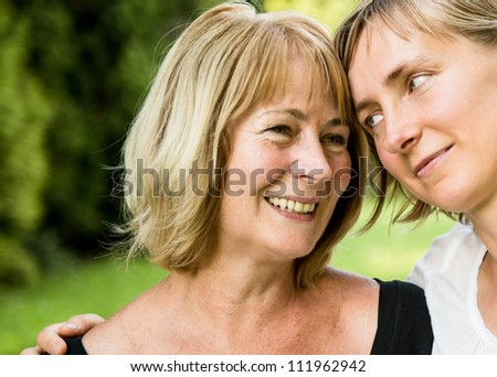 Outside portrait of smiling happy mature woman with her adult daughter