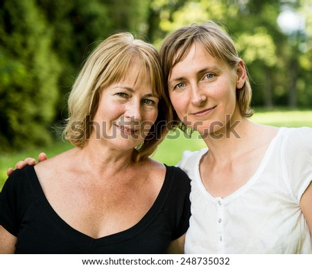 Outside portrait of smiling happy mature woman with her adult daughter - stock photo