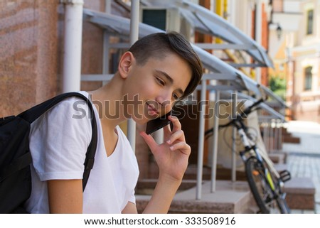 Outside portrait of teen boy. Handsome teenager carrying backpack on one shoulder and smiling, speaking by phone - stock photo