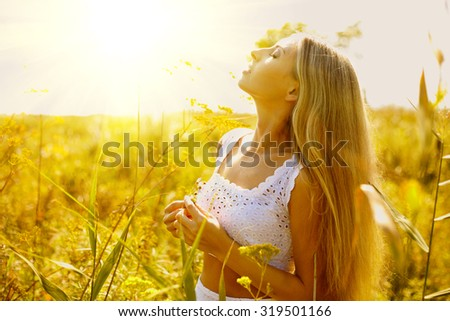 Outside portrait young woman in white dress in outside in the meadow under sunlight - stock photo