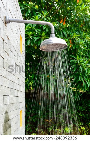 Outside shower with water spray at swimming pool - stock photo