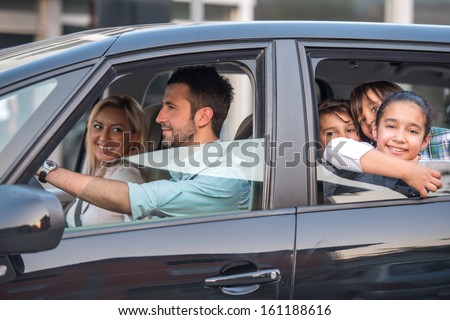 Outside view of a beautiful family driving in automobile - stock photo