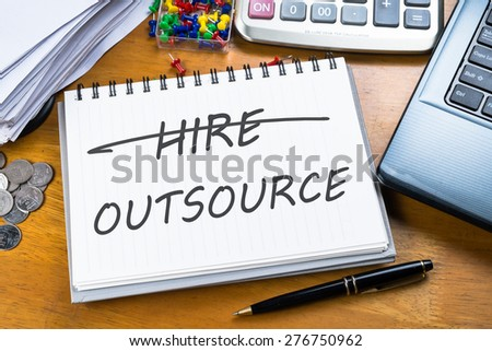 Outsource memo in notebook with part of laptop, receipts and calculator - stock photo