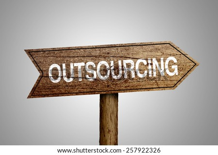 Outsourcing arrow wooden road sign is on gray background. - stock photo
